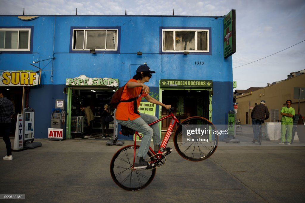 A cyclist rides past a pipe shop and The Green Doctors medical marijuana evaluation location in the Venice Beach neighborhood of Los Angeles, California, U.S., on Tuesday, Jan. 2, 2018. California launched legal marijuana Monday, and customers lined up to celebrate the historic moment in San Diego, Sacramento and Oakland -- some of the municipalities given the green light to start sales on January 1. Meantime, in Los Angeles and San Francisco, the state's first- and fourth-largest cities, customers were turned away empty handed. Photographer: Patrick T. Fallon/Bloomberg via Getty Images