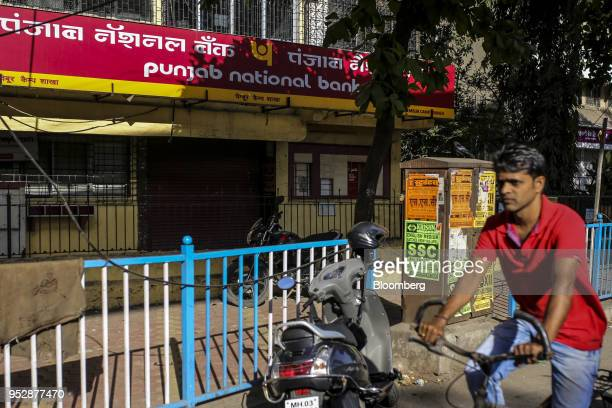 A cyclist rides past a Punjab National Bank branch in Mumbai India on Sunday April 22 2018 PNB is scheduled to announce full year earnings on May 16...