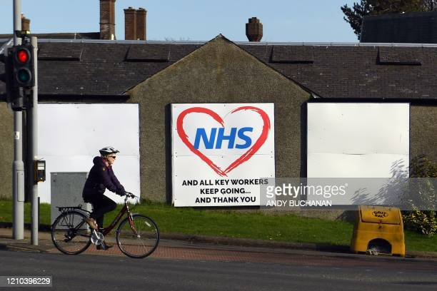 Cyclist rides past a sign paying tribute to NHS staff working during the COVID-19 illness outbreak in Glasgow on April 18, 2020. - The number of...
