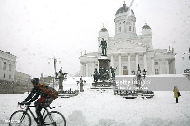 A cyclist rides past a snow covered Senate Square in Helsinki after snow storm hit Finland on March 26 2008 AFP PHOTO / LEHTIKUVA / Heikki Saukkomaa