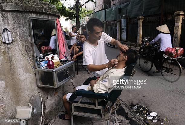 A cyclist rides past a street corner as barbers serve their customers at their openair road side shop in Hanoi on June 19 2013 A hair cut here costs...