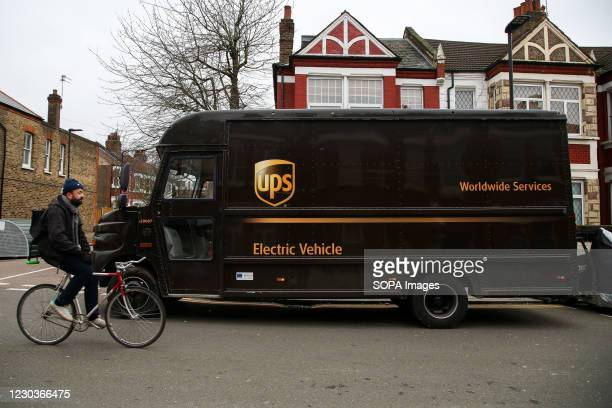 Cyclist rides past a UPS delivery van in London.