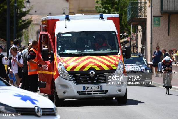 A cyclist rides past an ambulance car in which Team Ineos rider Great Britain's Christopher Froome receives medical treatment after falling on a...