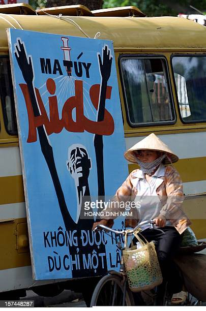 A cyclist rides past an antidrug poster with Vietnamese word Matuy meaning 'Drugs' during a street parade held 26 June 2001 in downtown Hanoi on the...