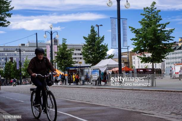 Cyclist rides past banners hanging from street lights promoting the city being the European green capital for the 2021 year in Lahti, where a pilot...