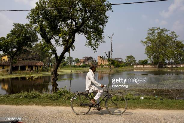 Cyclist rides past flood waters and the an abandoned sugar mill in Marhaura, Bihar, India, on Thursday, Oct. 22, 2020. Maintaining control of Bihar,...