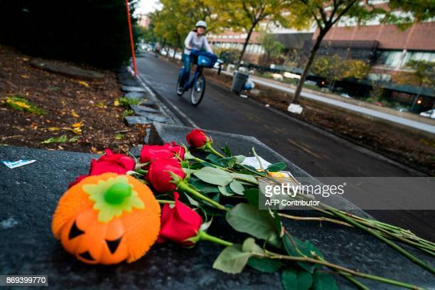 A cyclist rides past flowers left on a bike path to pay tribute to the October 31 terror attack victims in New York on November 2 2017 US President...