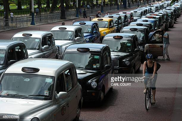 A cyclist rides past parked taxis during a protest by London Black Cab drivers against a new private taxi service 'Uber' a mobile phone app on the...