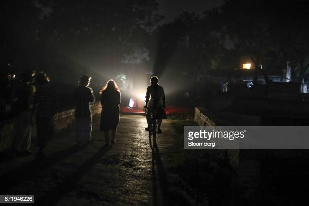 A cyclist rides past pedestrians on a street at night in Varanasi Uttar Pradesh India on Friday Oct 27 2017 In Varanasi where the manufacture of...