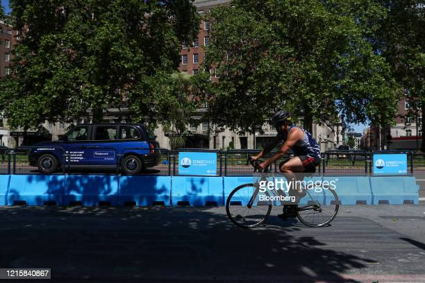 Cyclist rides past protective barriers in a new bicycle lane created by Transport for London on Park Lane in London, U.K., on Thursday, May 28, 2020....