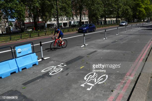 Cyclist rides past protective barriers on the outside of a new bicycle lane created by Transport for London on Park Lane in London, U.K., on...