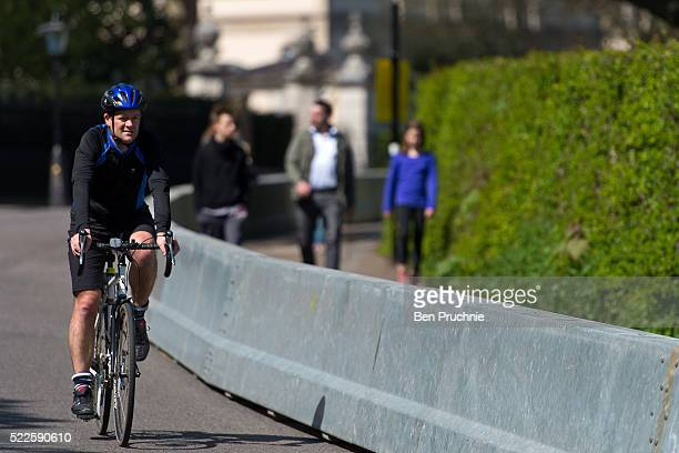 A cyclist rides past security barriers outside Winfield House in Regents Park ahead of US President Barack Obama's visit to the UK on April 20 2016...