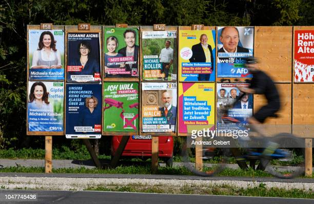 A cyclist rides past several election campaign posters on October 6 2018 in Bad Feilnbach Germany
