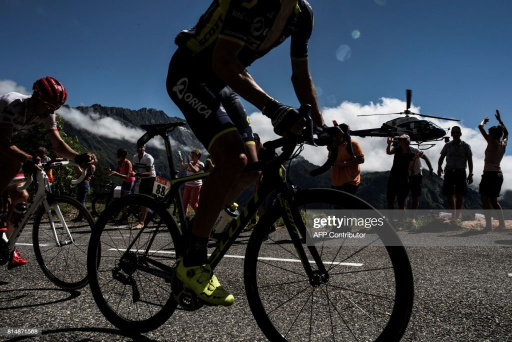 A cyclist rides past supporters as a media helicopter flies beside during the 101 km thirteenth stage of the 104th edition of the Tour de France cycling race on July 1, 2017 between Saint-Girons and Foix. / AFP PHOTO / Jeff PACHOUD