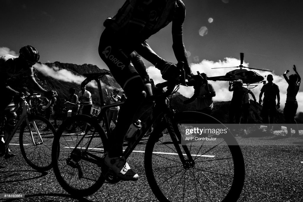 A cyclist rides past supporters as a media helicopter flies beside during the 101 km thirteenth stage of the 104th edition of the Tour de France cycling race on July 1, 2017 between Saint-Girons and Foix. /