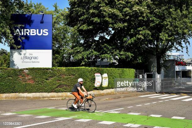 Cyclist rides past the Airbus logo outside the company headquarters in Blagnac, southern France, on June 30, 2020. - European aircraft maker Airbus...
