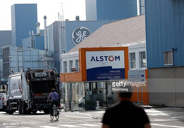 Cyclist rides past the entrance to the Alstom SA plant which sits adjacent to the General Electric Co.'s power-generation plant in Belfort, France,...