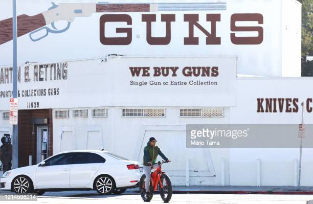 A cyclist rides past the Martin B Retting Inc guns store as the coronavirus pandemic continues on March 24 2020 in Culver City California LA County...