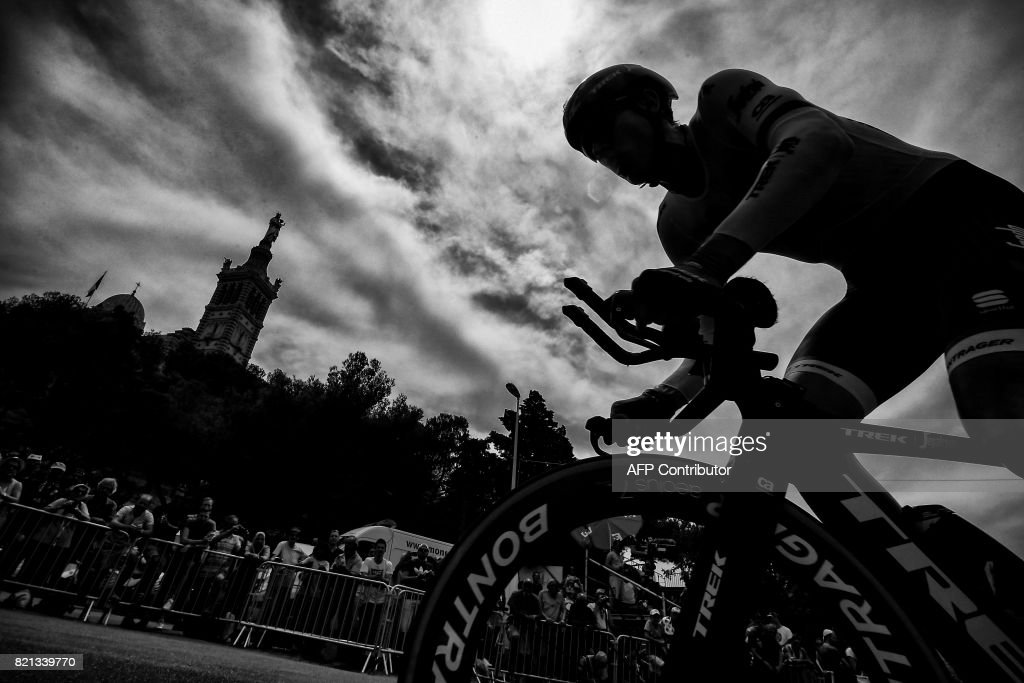 A cyclist rides past the Notre-Dame de la Garde basilica (L) as he competes in a 22,5 km individual time-trial, the twentieth stage of the 104th edition of the Tour de France cycling race on July 22, 2017 in and around Marseille, southern France. /