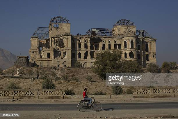 A cyclist rides past the ruins of the iconic Darulman Palace former home of the Afghan king which was damaged in the civil war in Kabul Afghanistan...