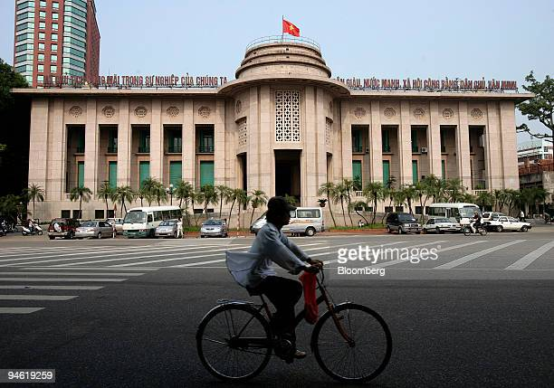 A cyclist rides past the State Bank of Vietnam in Hanoi Vietnam on Tuesday August 22 2006