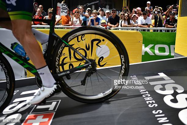A cyclist rides past the Tour de France's logo as he takes the start of the 17 km individual timetrial the eighteenth stage of the 103rd edition of...