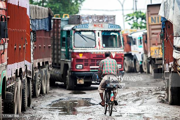 A cyclist rides past trucks parked at the Sanjay Gandhi Transport Naga depot in New Delhi India on Thursday Aug 22 2013 Indias rupee plunged 44...