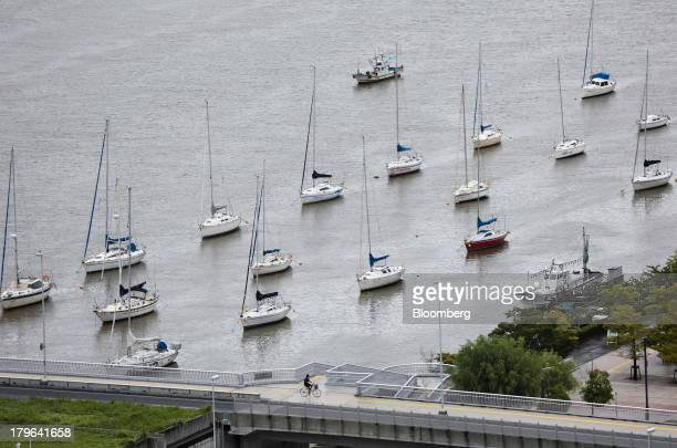 A cyclist rides past yachts moored in the Shinano river in Niigata Japan on Thursday Sept 5 2013 A government report on Sept 9 is forecast by...