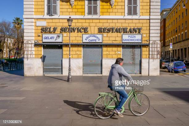 a cyclist rides the deserted streets of rome in front of a closed restaurant - industrial door stock pictures, royalty-free photos & images