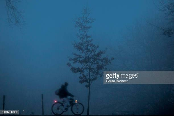 A cyclist rides through a forest during foggy weather on January 10 2018 in Berlin Germany