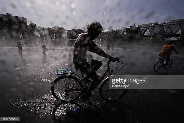 A cyclist rides through a fountain to cool down in the Madrid Rio playground on September 6 2016 in Madrid Spain A threeday heatwave has hit central...