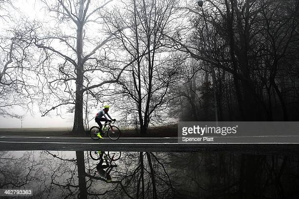 A cyclist rides through Brooklyn's Prospect Park on a morning with dense fog on January 15 2014 in New York City Travel delays were reported for...