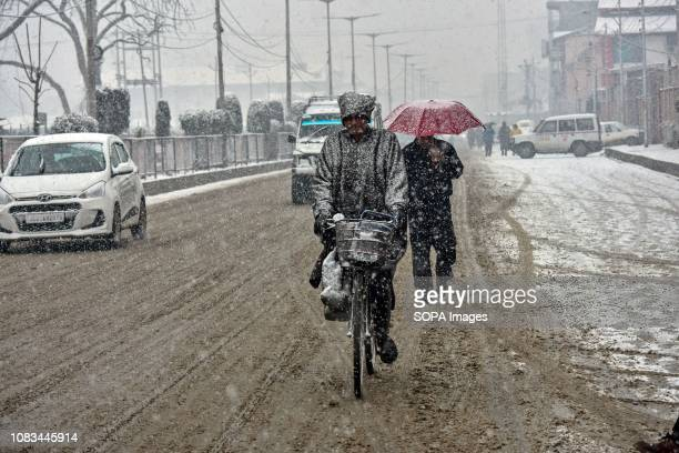 A cyclist rides through snow in Srinagar Indian administered Kashmir Fresh snowfall began in Kashmir valley breaking the intense cold wave conditions...