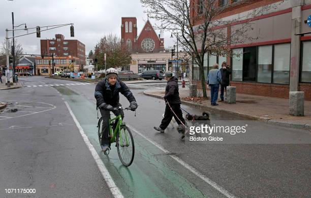A cyclist rides through Union Square in Somerville MA on Nov 26 2018 The square a jumble of hipster bars and ethnic restaurants auto shops and corner...