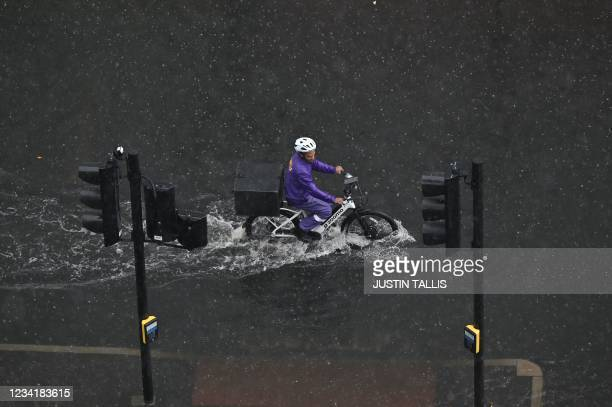 Cyclist rides through water on a flooded road in The Nine Elms district of London on July 25, 2021 during heavy rain. - Buses and cars were left...