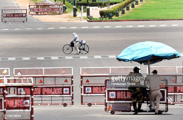 Cyclist rides while Delhi Police and security personnel stand under the shade of an umbrella as the temperature soars on a hot summer day at Raisina...
