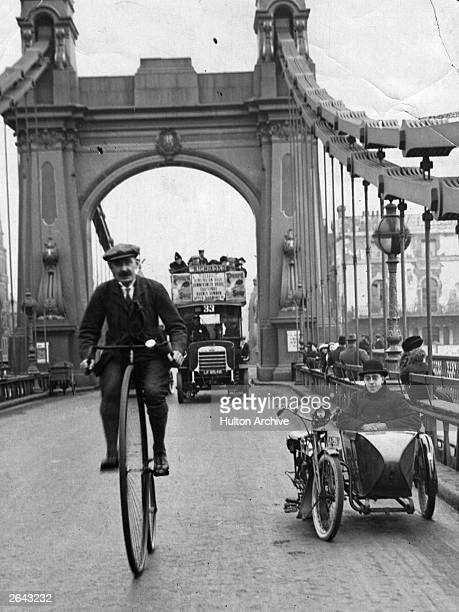 A cyclist riding a penny farthing over Hammersmith Bridge London