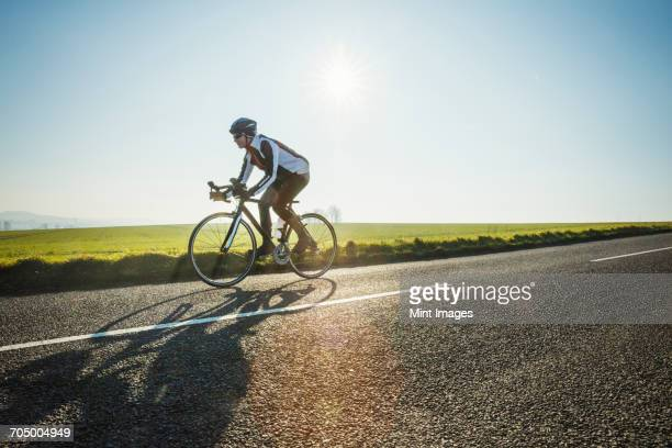 a cyclist riding along a country road on a clear sunny winter day. - wielrennen stockfoto's en -beelden