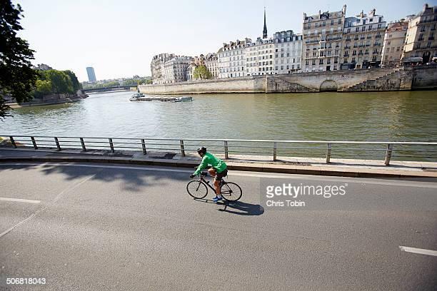 Cyclist riding along river Seine, Paris