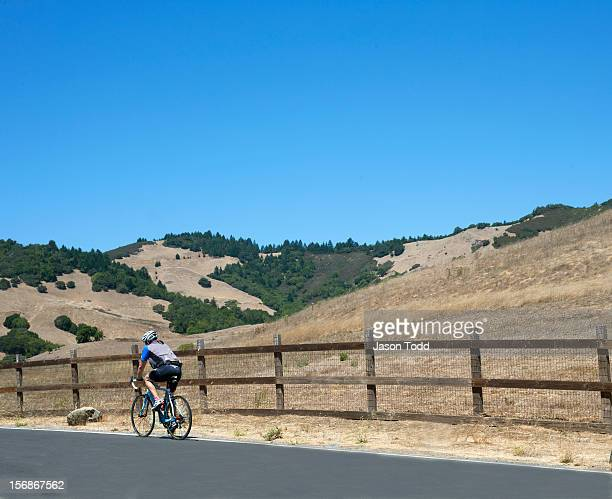 cyclist riding along scenic hilly road - san rafael california stock pictures, royalty-free photos & images