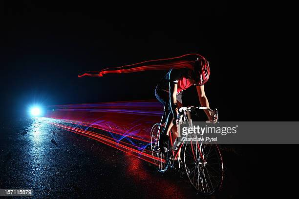 cyclist riding at night leaving streaks of light