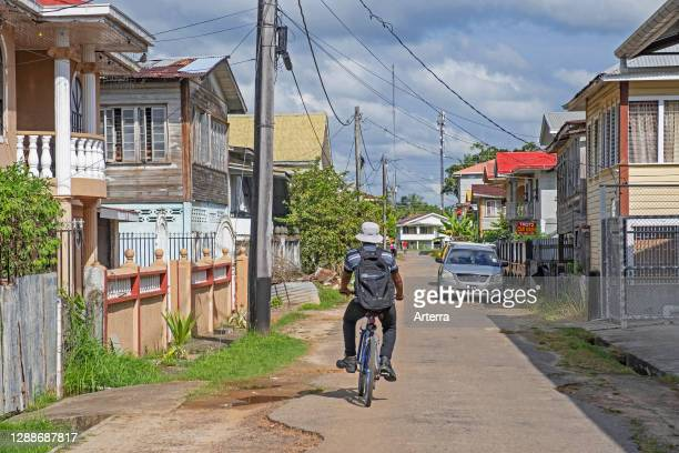Cyclist riding bicycle in the old city centre of New Amsterdam, East Berbice-Corentyne Region, Guyana, South America.