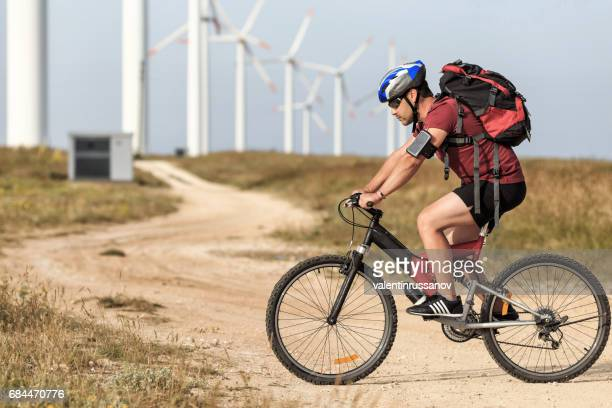 Cyclist riding in front of wind turbine farm