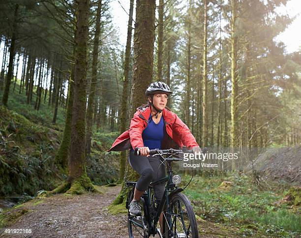 cyclist riding mountain bike through forest. - cycling helmet stock photos and pictures