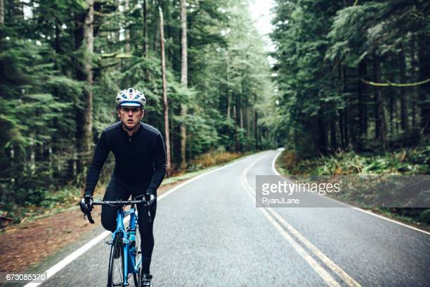 cyclist riding mountain road on racing bike - racing bicycle stock pictures, royalty-free photos & images