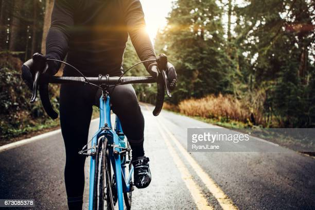 cyclist riding mountain road on racing bike - road cycling stock pictures, royalty-free photos & images