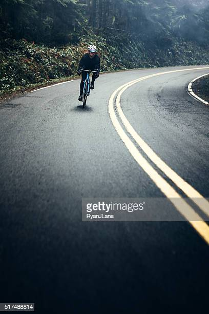cyclist riding mountain road - wielrennen stockfoto's en -beelden