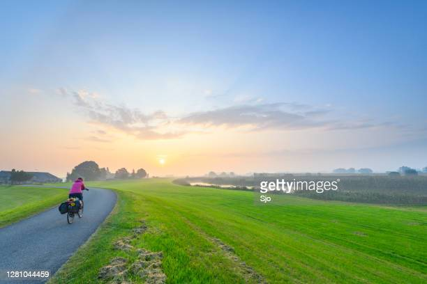"""cyclist riding on a levee during sunrise over the ijsseldelta landscape near kampen in overijssel - """"sjoerd van der wal"""" or """"sjo"""" stock pictures, royalty-free photos & images"""