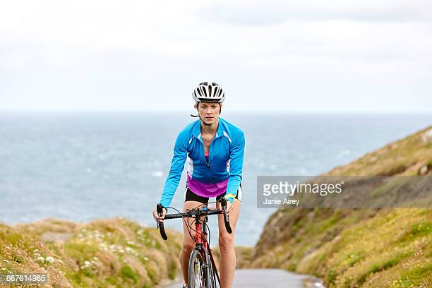 cyclist riding on road overlooking ocean - cycling helmet stock photos and pictures