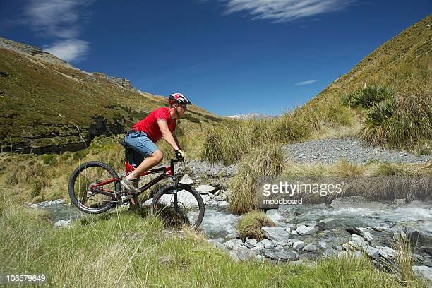 Cyclist riding through rocky field
